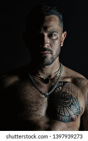 Bearded man with tattooed chest. Macho with sexy bare torso. Fit model with tattoo art on skin. Sportsman or athlete with stylish beard and hair. Sport and fitness. Confidence and masculinity.