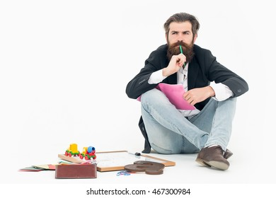Bearded man teacher with thoughtful face in black jacket and blue jeans holding green pencil in his mouth and pink exercise book in hand sitting near school stationery isolated on white background