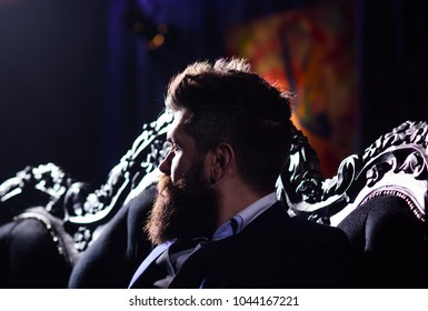 Bearded man with thoughtful face in classic interior. Luxury lifestyle, confidence, success, fashion concept. Millionaire in elegant suit sits on luxurious sofa. Brutal man or boss with long beard.