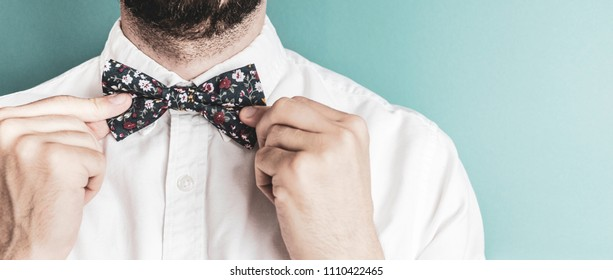 Bearded man tightening up a floral patterned bow tie on a pastel blue background. Vintage filter is used. Negative space on the right, close up.