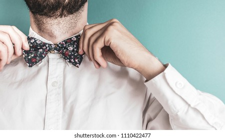 Bearded man tightening up a floral patterned bow tie on a pastel blue background. Vintage filter is used.