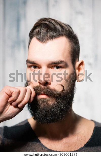 Bearded man touches his mustache. Close-up shot on bright background. Shallow depth of field.
