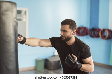Bearded man training with punching bag boxing in gym