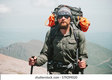 Bearded Man traveler hiking in mountains with backpack Travel Lifestyle concept adventure active vacations outdoor mountaineering sport