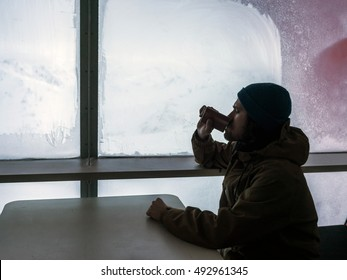 Bearded man traveler inside the hotel with flask in his hand looking out the window at the beautiful snow-covered mountain landscape