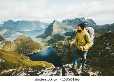 Bearded man traveler standing on cliff mountain in Norway Traveling with backpack healthy lifestyle adventure concept hiking active summer vacations outdoor