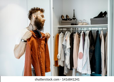 Bearded man trying shirt, choosing clothes to wear in the wardrobe at home