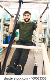 Bearded man using a cadillac for abs exercises , inside of a gym
