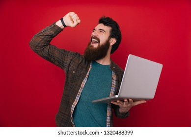 Bearded man using computer laptop very happy and excited, winner expression celebrating victory screaming with big smile and raised hands.