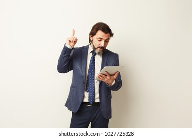 Bearded man using tablet computer, found something interesting, raising hand upwards, success concept. Businessman reading news, chatting, online shopping, surfing the net.
