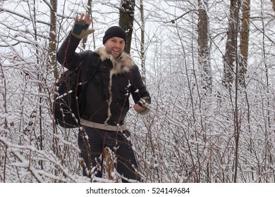 bearded man walking in a winter park snow season