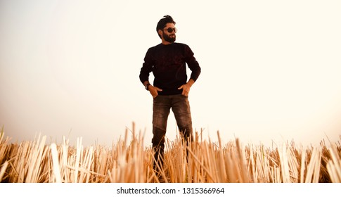 A bearded man wearing black dress standing around an agricultural field