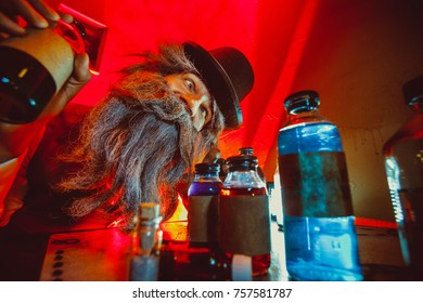 Bearded man wearing black hat and vest with the lantern. Medicine man in Dickens style.