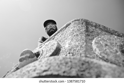 A bearded man wearing a cap and sunglass standing in a place