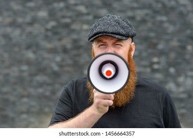 Bearded man wearing a cloth cap speaking into a megaphone making an announcement or public speaking