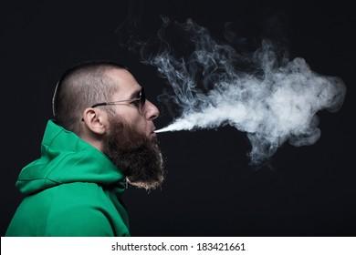 Bearded man, wearing a green sweatshirt and sunglasses, smoking
