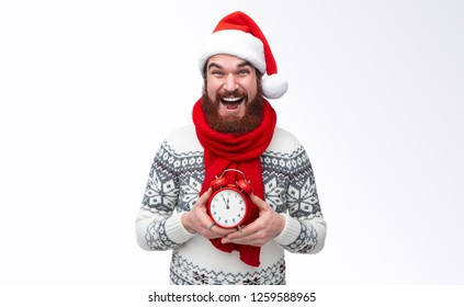 Bearded man wearing red santa hat and warm winter pullover holding clock five to twelfe and waiting for christmas countdown isolated on white background