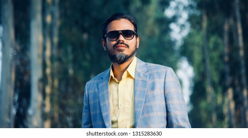 A bearded man wearing suits standing in a place