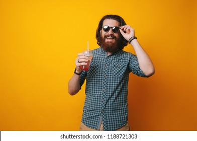 Bearded Man wearing sunglasses and holsing a glass of juice on yellow background.