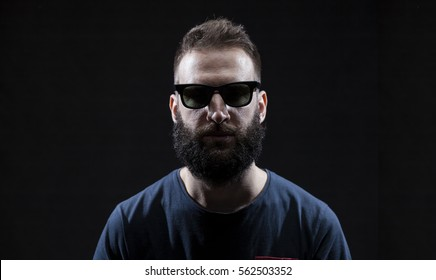 Bearded man wearing sunglasses isolated on black background, low key portrait