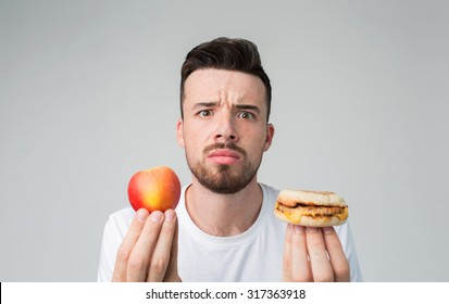 Bearded man in a white shirt on a light background holding a hamburger and an apple Man makes the choice between fast and healthy food. Tasty or useful? The dilemma choosing a different lifestyle