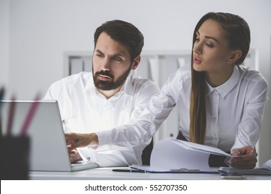 Bearded man in a white shirt and a woman with long hair are working in an office. She is holding a document attached to a clipboard. He is looking at a laptop screen