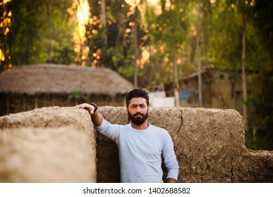 A bearded man in a white t shirt standing in a place unique photo