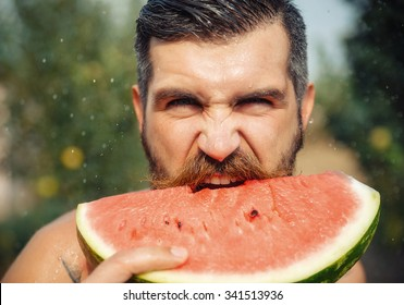 bearded man without clothes with a big juicy ripe watermelon in hands on a background of flowering garden illuminated by bright sunshine