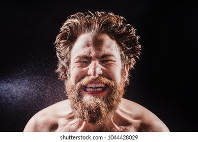 A bearded man without a shirt shouts in a spray of water against a black background. portrait view
