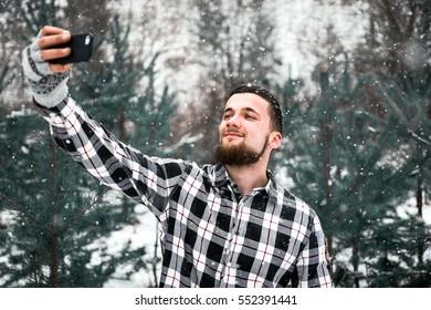 Bearded man in the woods makes selfie. Selfies time