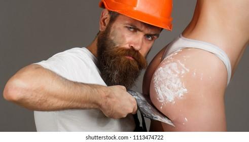 Bearded man worker, beard. Female ass in underwear. Plastering tools. Naked body. Big ass, gorgeous bum, sexy girl. Tool, trowel, handyman, man builder. Ass, bum, butt. Builders in hard hat, helmet.