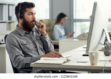 Bearded man at working desk in office using computer and speaking to client in headset