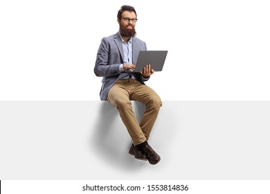 Bearded man working on a laptop and sitting on a banner isolated on white background