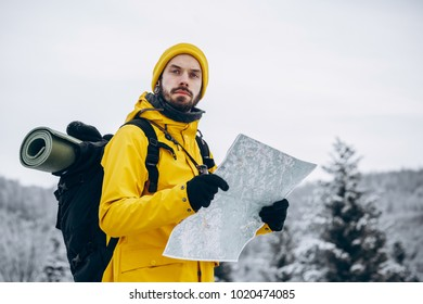 Bearded man in yellow winter closes hikes in the forest over the winter mountains covered with snow and reads a map in his hands