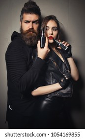Bearded man and young woman smoking e-cigarettes with lowe angle view off the middle-aged man exhaling smoke from his nostrils in the foreground. Couple resting in vape shop, to let smoke out of mouth