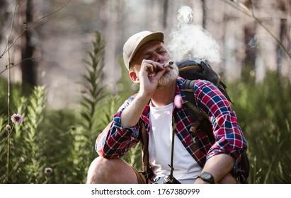 Bearded mature man smoking medical marijuana in nature.