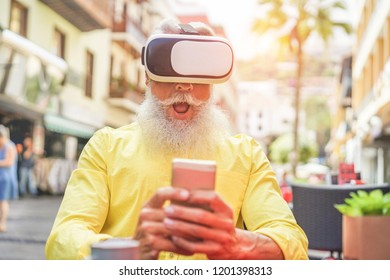 Bearded mature man wearing virtual reality goggles with smartphone in bar outdoor - Senior trendy male using vr headset - New technology trend and joyful elderly lifestyle concept - Focus on his mouth