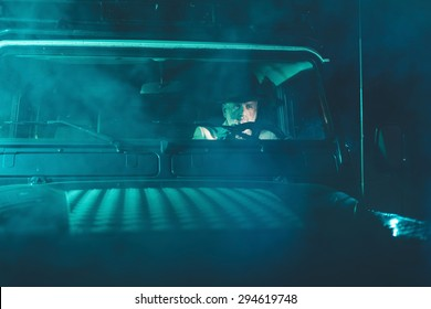 Bearded Matured Guy Wearing a Hat, Driving a 4x4 Vehicle in the Middle of the Night with Pensive Facial Expression.