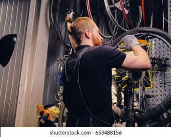 Bearded mechanic repairing bicycle wheel tire in a workshop. Back view, service manual.