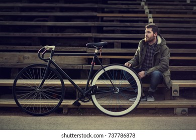 Bearded men with green jacket sitting on the stairs with a vintage bicycle near him with a white wheel.