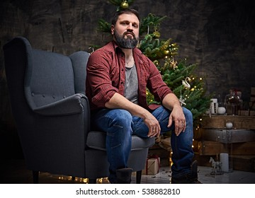 A bearded middle age male dressed in a plaid shirt and jeans sits on a chair over Christmas illumination and fir tree in background.