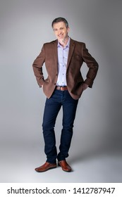 Bearded middle aged fashion model posing with business casual style outfit for mature and confident look.  The trendy brown jacket and jeans and facial hair shows an elegant apparel.