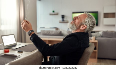 Bearded middle-aged man, artist smoking a marijuana cigarette or joint, sitting at home, in the kitchen and writing song using laptop. Marijuana grinder on the table. Cannabis legalization concept