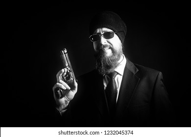 bearded middle-aged man in a knitted black hat in suit with hat and sunglasses is holding pistol in hand on dark background.