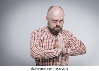 The bearded middle-aged man praying with hands folded, with an angry look on a gray background