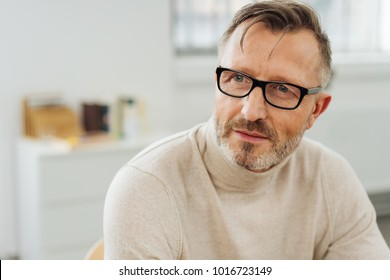Bearded middle-aged man wearing glasses sitting in an office staring to the side with an attentive expression as though waiting for a response or pondering a problem