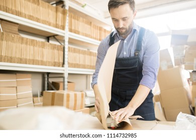 Bearded middle-aged worker wearing checked shirt and jumpsuit packing pressure transducers while standing at spacious warehouse of measuring equipment factory