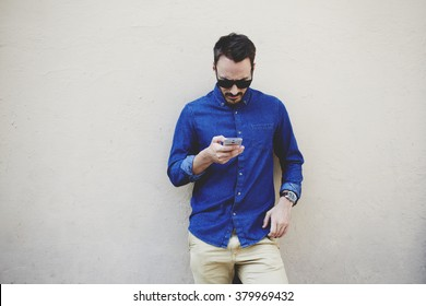 Bearded modern businessman concentrated reading world news in internet via mobile phone during work break, hipster guy watching video on cell telephone while standing against wall with copy space area