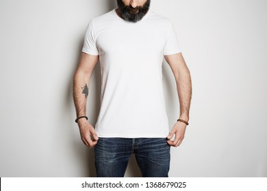Bearded muscular man model wearing white blank t-shirt with space for your logo or design in casual urban style on the white background