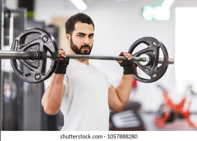 Bearded muscular man wears white t-shirt have workout with barbell in the gym